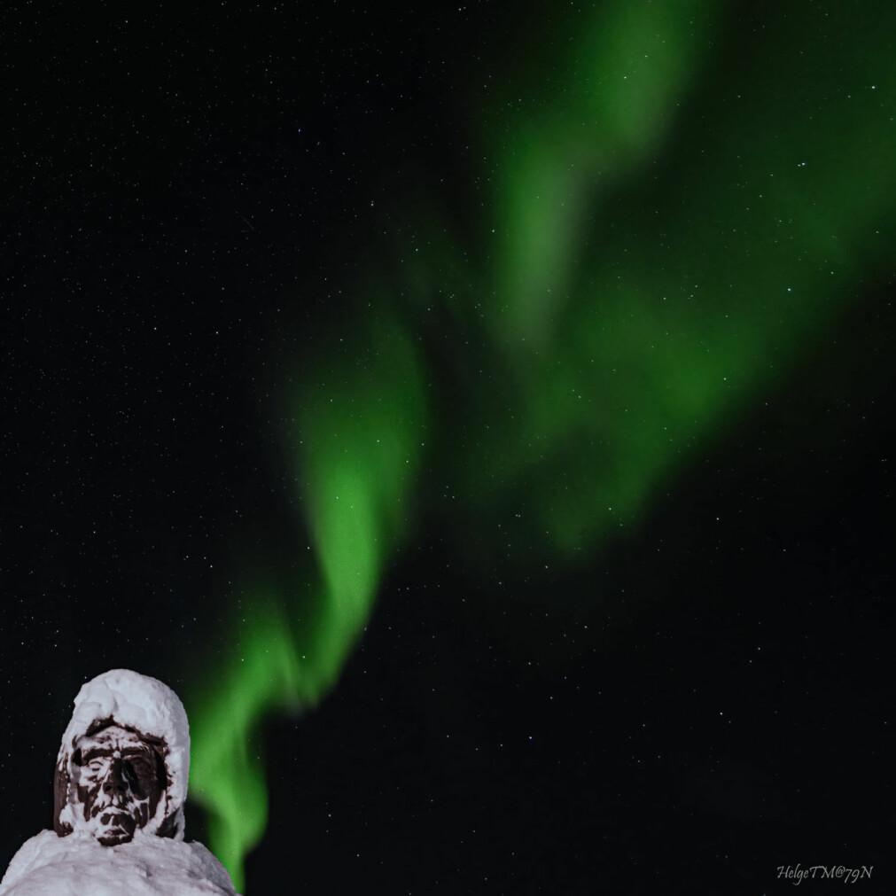 Statuen av Roald Amundsen i Ny-Ålesund lyser opp under nordlyset. Bildet ble tatt en snørik dag i oktober.