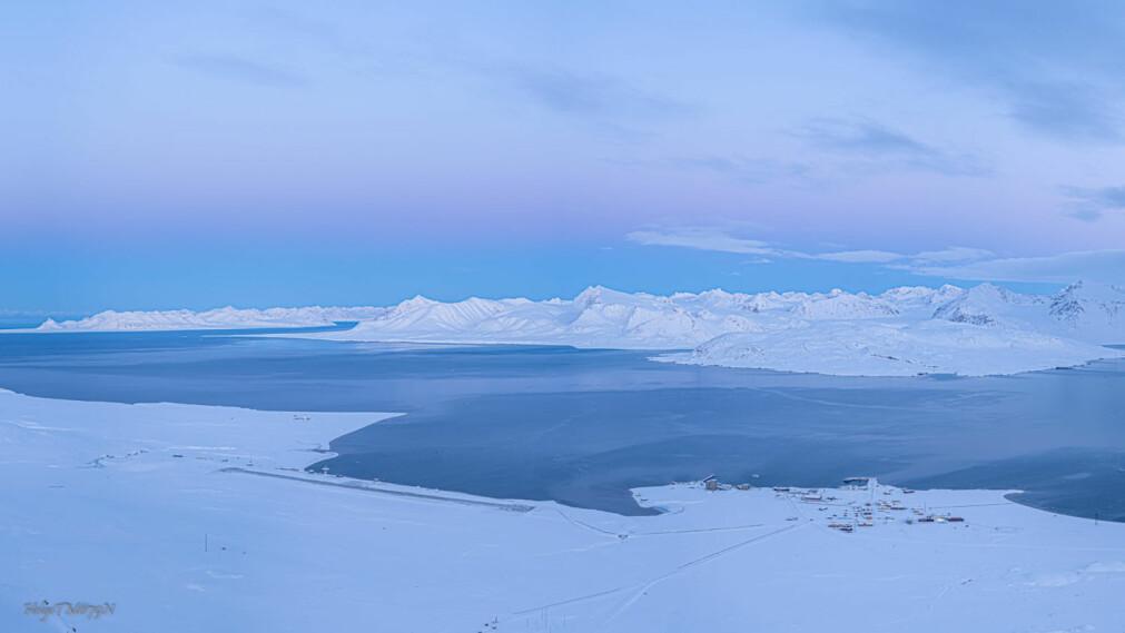 Ny-Ålesund sett fra flyvinduet en godværsdag, mens det fortsatt var dagslys tidligere i høst.