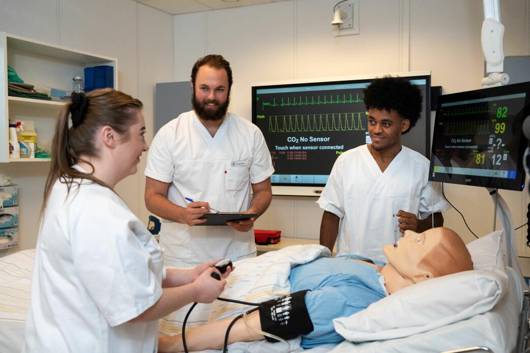 Sjukepleiarstudentar ved UiA speler rollespel med pasientdokker for å øve på akutte endringar hos pasienten.