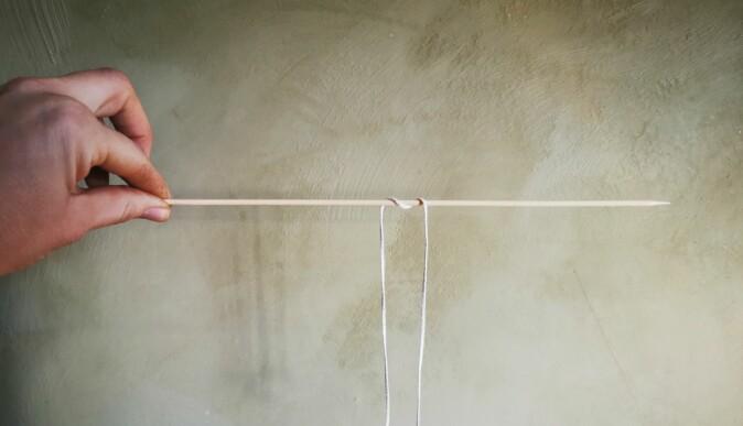Heng veken over et trespyd eller en pinne og la den henge ned et stykke på begge sider. Bind en mutter i enden, så synker den til bunns i bivoksen og lyset holder seg rett.