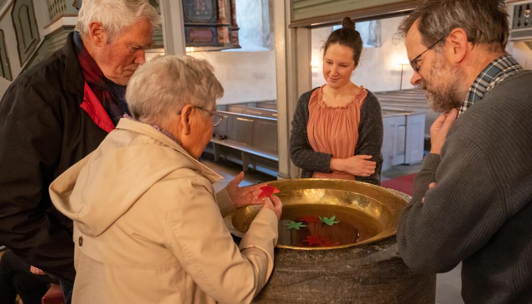 Forsking på demens trenger ikke å skje på et laboratorium. Det kan like gjerne skje i møte med folk. Her er det samling rundt døpefonten og lapper med korte budskap, under et kunstarrangement i Trondenes kirke i Harstad.