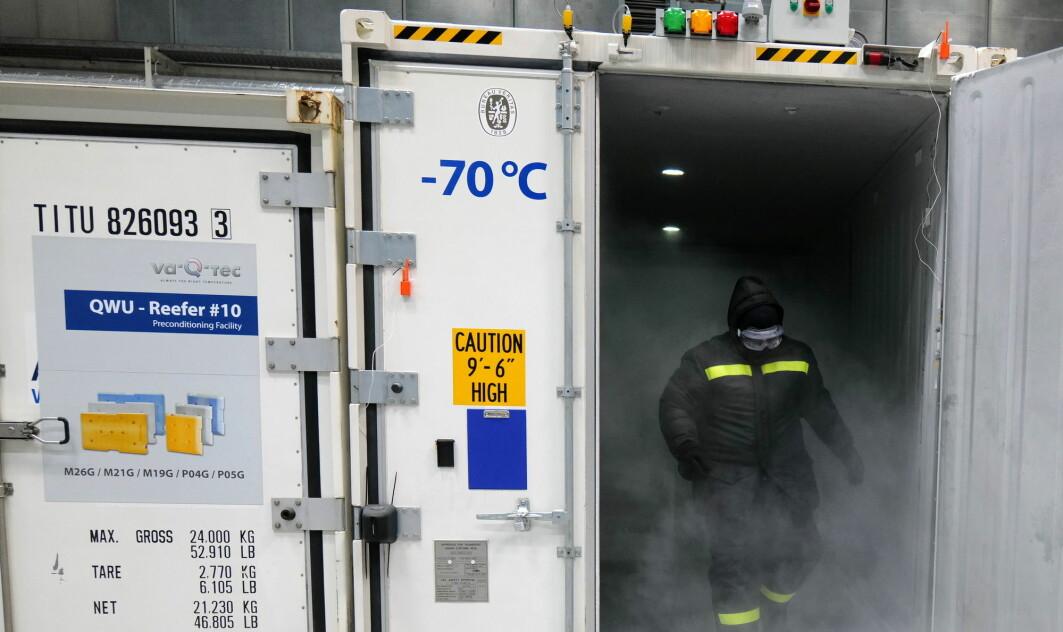 En ansatt ved et tysk logistikkselskap fyller en container med tørris slik at den kan brukes til å frakte koronavaksiner.