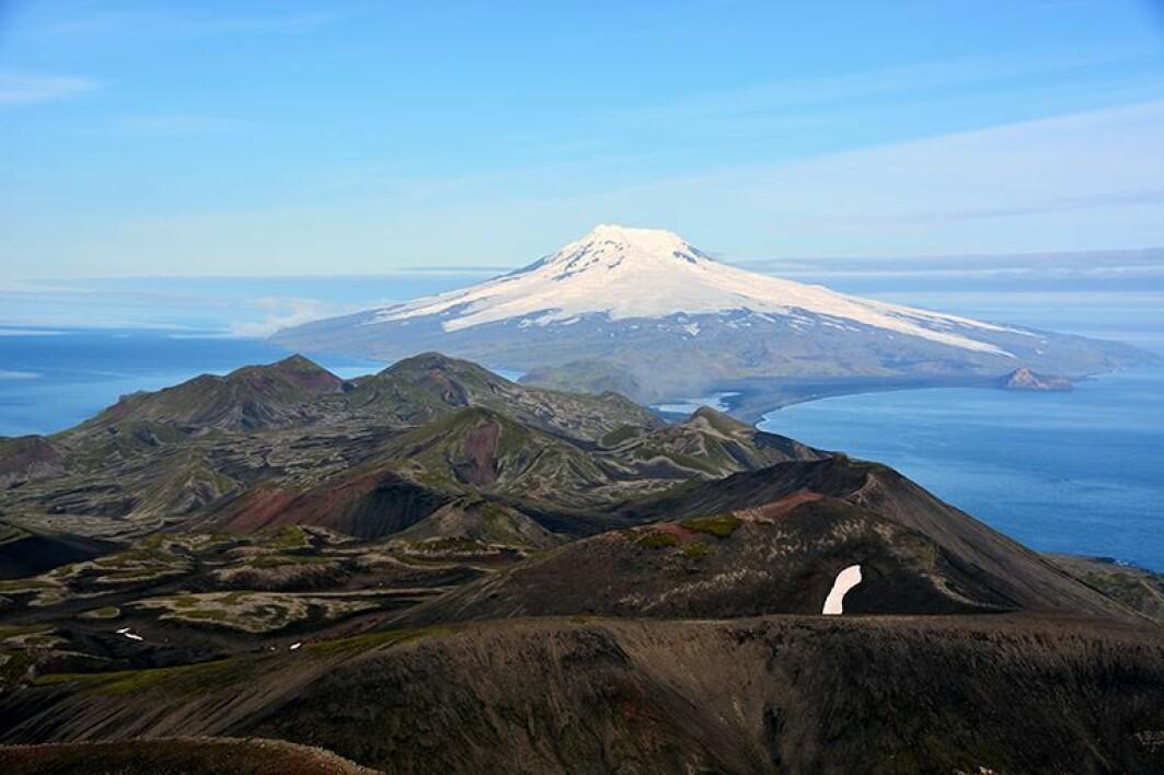 Utsikt over det vulkanske landskapet som dominerer på Jan Mayen. Lengst bak synes vulkanen Beerenberg, som er dekket av isbreer.