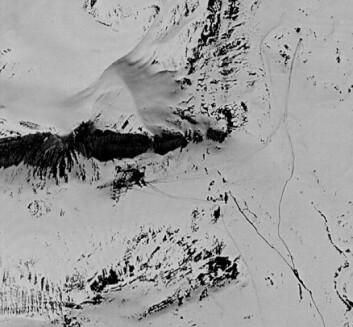 """""""Dette satellittbildet er tatt våren 1970 og dekker omtrent det samme området som forrige bilde. Det mørke feltet som går inn i bildet fra venstre er skyggen av selve fjellet. Flekken under der igjen er selve basen. Stripene som er tydelige, er spor etter kjøretøy i snøen. Basen var nok under bygging da bildet ble tatt, og er klart den største basen som ble bygget her, sett bort fra hovedbasen ved kysten."""""""