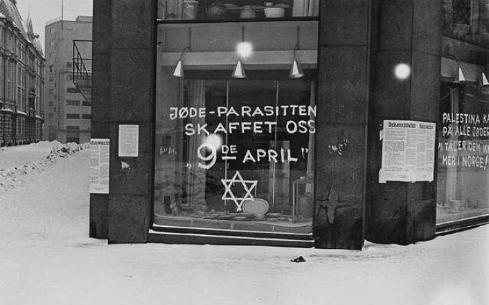 """Antisemittisk grafitti på et butikkvindu i Oslo i 1941. Teksten på vinduet i forgrunnen sier """"Jøde-parasitten skaffet oss 9de april"""". På ruta rundt hjørnet står """"Palestina kaller på alle jøder. Vi tåler dem ikke mer i Norge"""". (Foto: Anders Beer Wilse (1865–1949)/Wikimedia Commons)"""