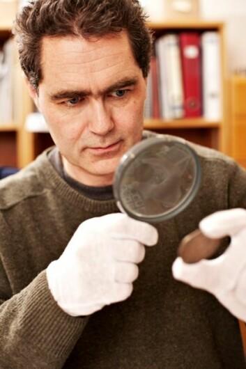 Afghanistan er det store temaet på NTNU Vitenskapsmuseet i år, og museets myntekspert Jon Anders Risvaag har tatt fram en over tusen år gammel myntskatt fra det fjerne landet. (Foto: NTNU Vitenskapsmuseet/Geir Mogen)