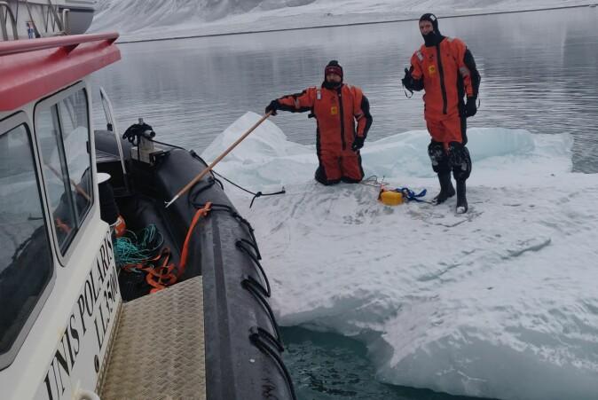 Aleksey Marchenko fra Universitetssenteret på Svalbard (UNIS) og Trygve Kvåle Løken (t.h.) gjør isfjellet klart til taueeksperiment.