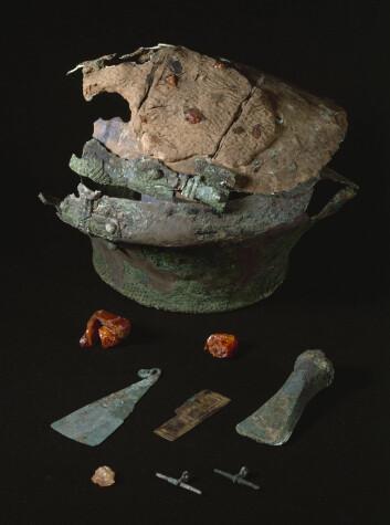 Fra innholdet i graven på Sørvestfyn i Danmark, der Lusehøj-tøysykket ble funnet: På bildet ses bronseurnen, andre gjenstander i bronse og rav. (Foto: (Foto med tillatelse fra Nationalmuseet, Danmark))