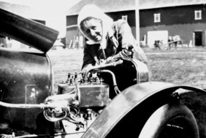 Thora Løken var første kvinne som tok sertifikat i Hedmark i 1914. Her mekker hun på bilen sin utenfor Granerud gård i Veldre. (Foto: Ukjent person/Hedmarksmuseet)