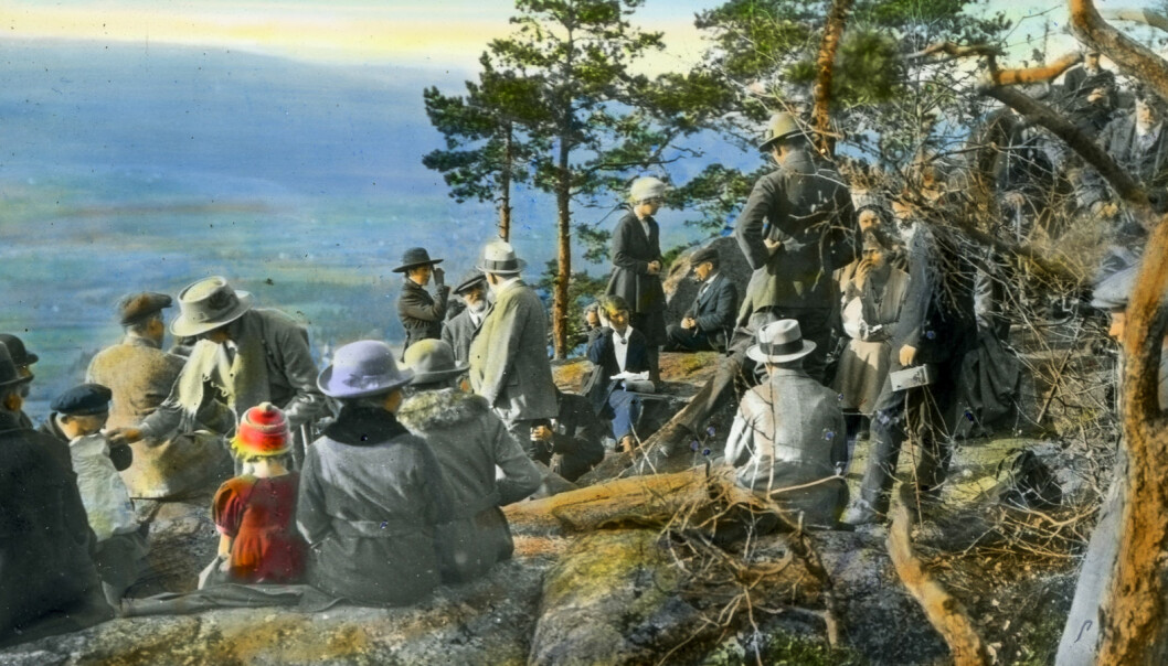 "During the interwar period, a growing number of hikers visited Oslomarka, where they could follow the multiplying choice of paths waymarked with blue blazes. The association for ""Friluftsliv og Kropskultur"" (outdoor pursuits and physical culture) gathered at Kolsåstoppen in Bærum in the summer of 1920. Hand-coloured photograph."
