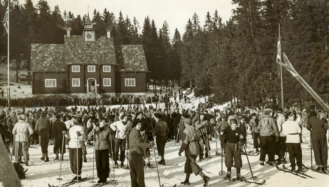 Sunshine and, most probably, good conditions for skiing: Large group skiing in front of the old Ski Museum at Frognerseteren, 1920s.