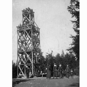 Tryvannstårnet tower was a popular destination for hikes as early as 1863, when the first observation tower was built by Thomas Heftye. The photograph shows the second tower, ca. 1920.