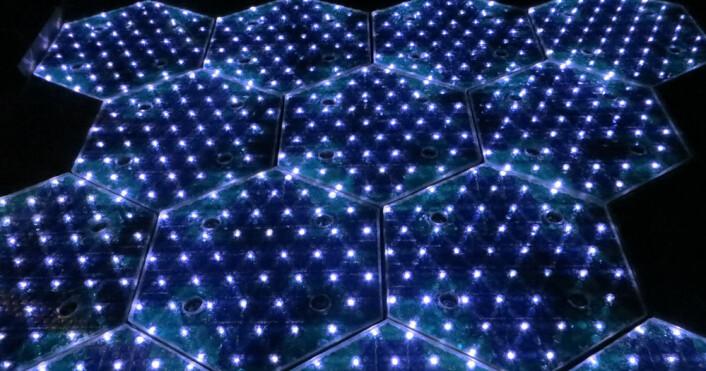 De sekskantede glasskivene med solceller inneholder også lysdioder, trykkfølere, elektronikk for kommunikasjon og i noen tilfelle også varmeelementer for bruk i kalde områder, slik at veiene blir snø- og isfrie. (Foto: Solar Roadways)