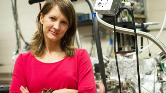 Forsker Charlotte Sanders i teamet som står bak verdens minste nanolaser. Bak Sanders skimter vi en av maskinene som er brukt for å lage laseren. (Foto: Alex Wang, University of Texas)