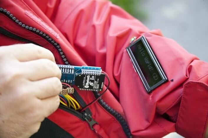 I stedet for et telefondisplay er det sydd på et display på jakkeermet som viser en linje med rulletekst, og mottakeren føler en liten vibrasjon i kragen når en melding blir mottatt. (Foto: Gry Karin Stimo/Sintef)