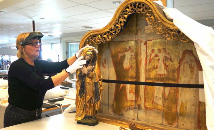 Tone Olstad med Mariaskulpturen, som nå er tatt ut av alterskapet fra Ørsta kirke sammen med de andre treskulpturene for å restaureres. (Foto: Arnfinn Christensen)