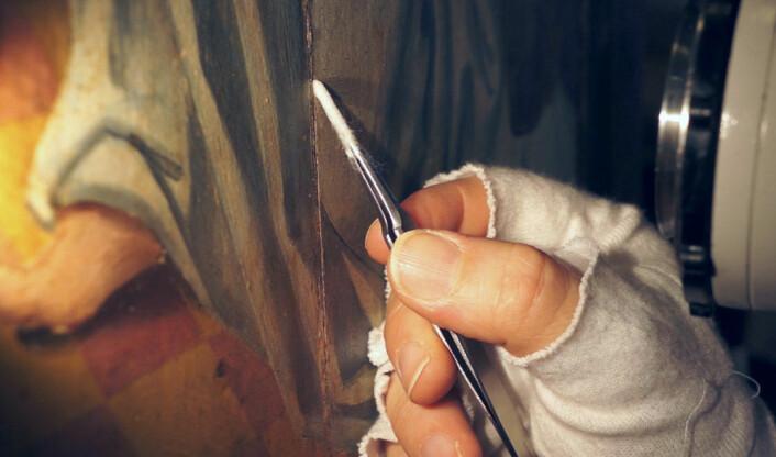 Malerikonservator Barbro Wedvik ved Norsk institutt for kulturminneforskning fjerner lim som kan skade malingen på døren til alterskapet i Ørsta kirke. (Foto: Arnfinn Christensen)