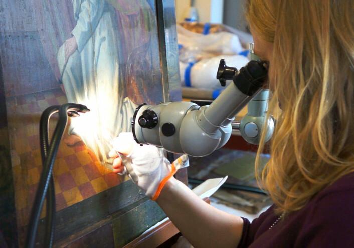 Barbro Wedvik arbeider med lupe og pinsett for å fjerne lim som kan skade malingen på maleriet av engelen på døra til alterskapet fra Ørsta kirke. (Foto: Arnfinn Christensen)