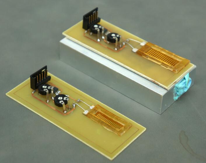 To prototyper av energihøsteren basert på en strømledende dråpe som glir over elektroder, utviklet ved Institutt for mikro- og nanoteknologi ved Høgskolen i Vestfold. (Foto: Arnfinn Christensen)