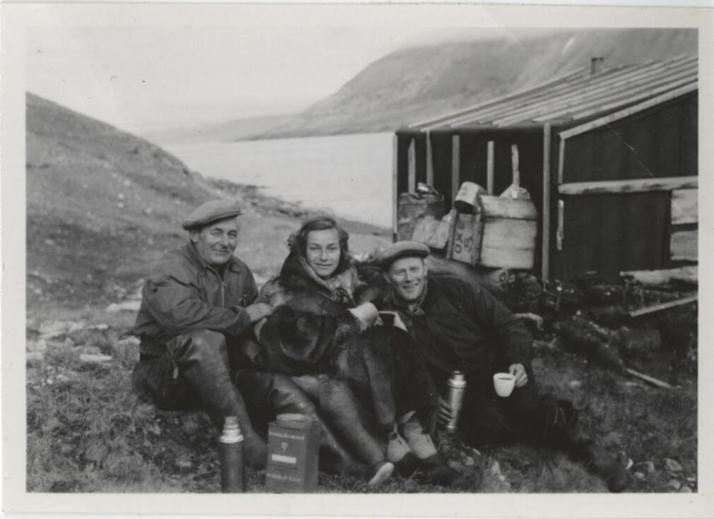 Brit Hofseth sammen med fangstmennene Henry Rudi (t.v.) og Schjølberg Nilsen utenfor en fangsthytte på Revet på Grønland.