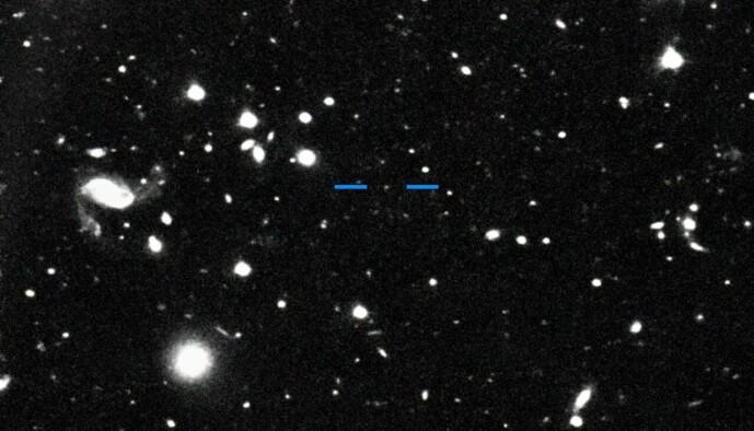 Her er et av bildene forskerne har tatt av Farfarout. De store hvite flekkene er stjerner og galakser i bakgrunnen, mens Farfarout er den bitte lille prikken mellom de blå strekene.