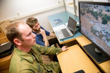 Oberstløytnant Geir Karlsen ser etter utplasserte kamuflerte mannekenger i varierende terreng i en test utviklet av FFI. I bakgrunnen forsker Gorm Krogh Selj. (Foto: FFI)
