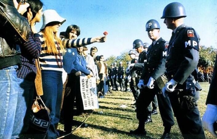 En kvinnelig demonstrant rekker fram en blomst til amerikansk militærpoliti i 1967. (Foto: Wikimedia Commons)