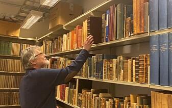 """Polarbibliotekar Ivar Stokkeland oppbevarer boka <span class="""" italic"""" data-lab-italic_desktop=""""italic"""">Historien om de nordiske folk</span> bak lås og slå."""