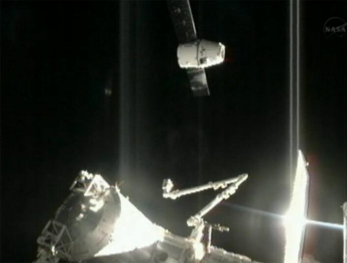 Romkapselen Dragon ankommer Den internasjonale romstasjonen 10.oktober 2012 med den første ordinære lasten. Nederst sees robotarmen Canadarm2, som skal strekkes ut for å fange inn Dragon. (Foto: NASA)