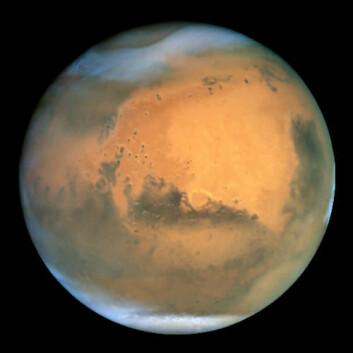 Mars, sett fra avstand. Nærmere enn dette kommer nok ikke menneskelige øyne i løpet av de neste tiårene. (Foto: NASA)