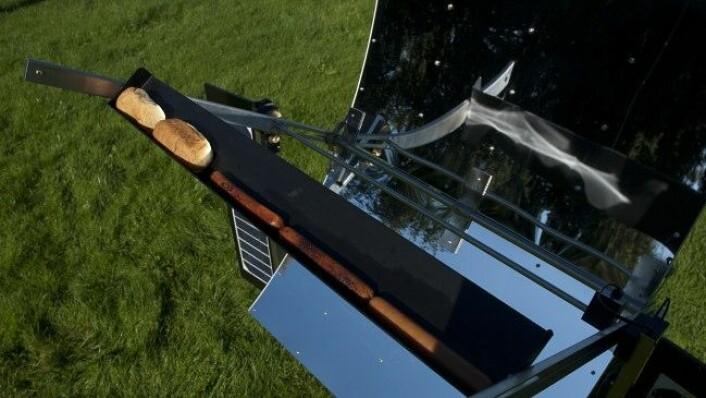 Dette er verdas einaste solcellegrill. Pølsene blir grilla på ei smal steikeplate som blir varma opp av sola. Solceller gir straumen som trengst for å styre spegelen etter sola. (Foto: Helga Maria Sulen Sund/NTNU)