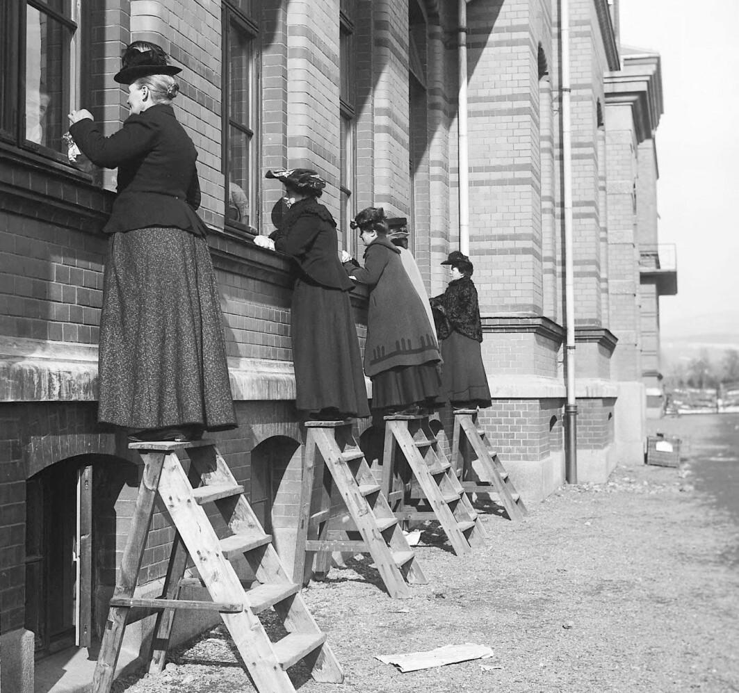 Bildet er fra 1905 og tatt under en difteriepidemi på Ullevål sykehus. Infeksjonssykdommer florerte, særlig der folk bodde trangt. Disse kvinnene besøker slektninger som er innlagt på sykehuset, men må stå utenfor for å unngå å bli smittet.