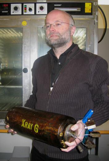 """""""Ingebret Fjelde holder kjerneholderne inne på laboratoriet på IRIS. Inne i disse skal de legge sedimentkjerner sauset inn med olje som skal flømmes med CO2. (Foto: Reidar Müller)"""""""