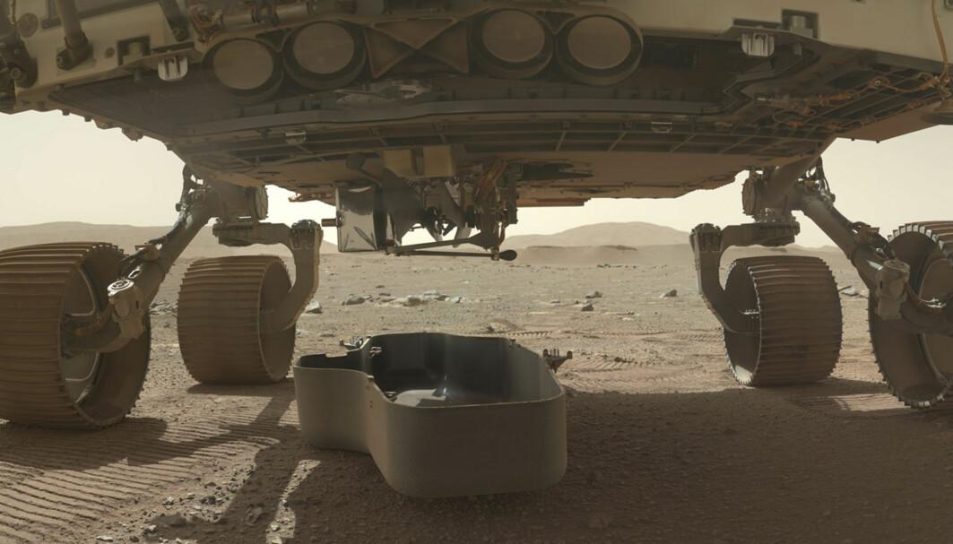 Et bilde offentliggjort av Nasa søndag viser den lille helikopterdronen Ingenuity, som er brettet sammen og koblet fast til undersiden av robotfarkosten Perseverance på Mars. Skjoldet som har beskyttet den, er nylig koblet fra. Det kan ses på bakken under.