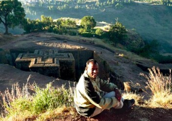 Den etiopiske NTNU-kjemikeren Kitane Fanta Gebremariam på hjemlige trakter. St. Georgskirken i Lalibela ble hugget ut av fjellet, under bakkenivå, tidlig på 1200-tallet. Det er altså taket vi ser. Kirken har blitt kalt verdens åttende underverk. (Foto: Lise Kvittingen)