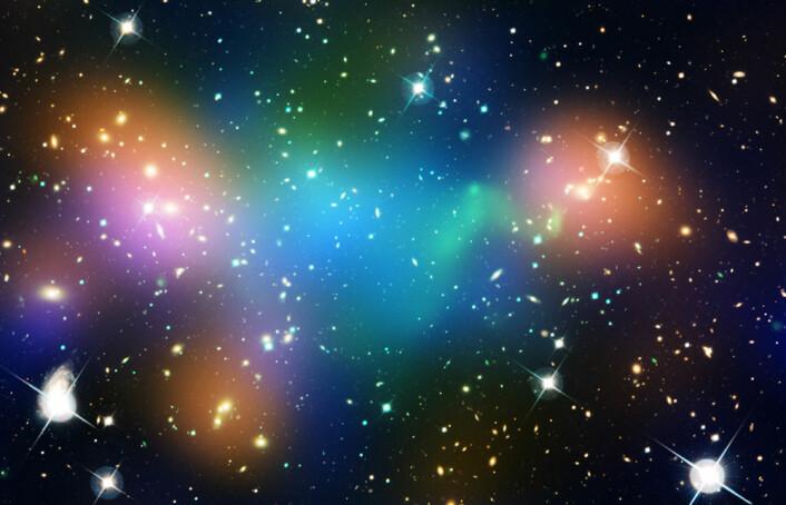 Bildet viser kjernen i galaksehopen Abell 520. Fargene er lagt på for å vise hvor de ulike komponentene i hovedsak befinner seg. Galakselyset er markert med oransje. Varm gass, et av tegnene på at galaksehoper har krasjet, er farget grønn. Mørk materie er farget blå. (Foto: NASA, ESA, CFHT, CXO, M.J. Jee (University of California, Davis), and A. Mahdavi (San Francisco State University))