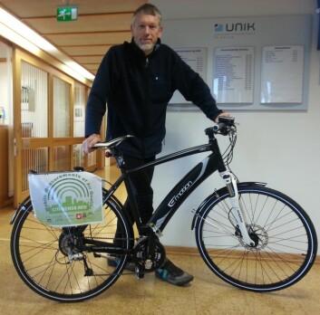 Professor Josef Noll ved Universitetssenteret på Kjeller (Unik) viser fram elsykkelen som er tilpasset slik at man kan sykle og måle luftkvaliteten samtidig. (Foto: Unik)