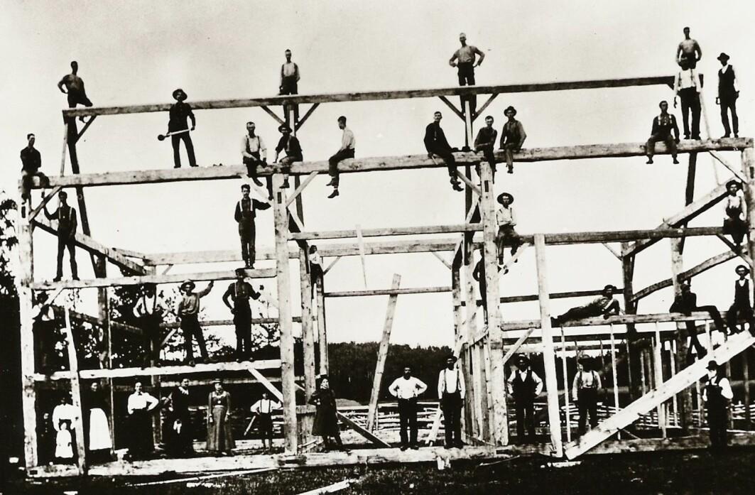 Da familiene fant et velegnet sted å etablere seg, trengte de hjelp til bygging. Dette bilde er fra Montana i 1895 og viser en låve under bygging, tilsynelatende i god norsk dugnadstradisjon.