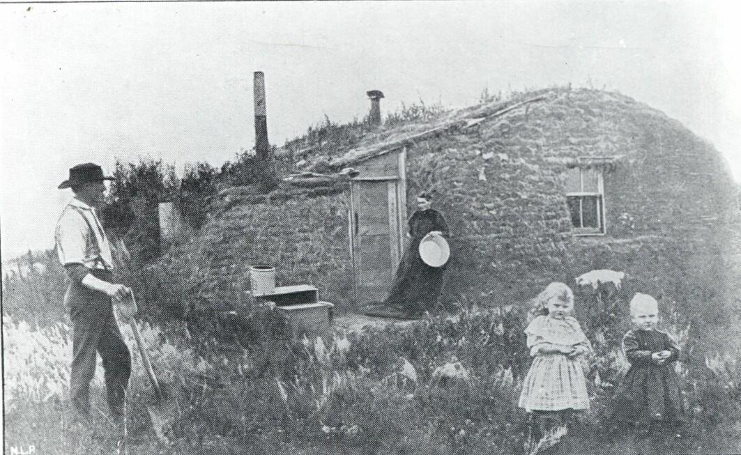 Nybyggerne bygde ofte hus av torv. Torvhusene holdt godt på varmen, noe som var helt nødvendig i de harde vintrene. Bildet viser nybyggeren John Bakkens første hus i Milton i Cavalier County, North Dakota, cirka 1880.