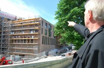 Marius Nygaard teller etasjer og viser vindusløsninger på et av nybyggene ved Vulkan i Oslo. Ting som her er gjort i teglstein og stål, kunne like gjerne vært laget av tre, mener han. (Foto: Hanne Østli Jakobsen)