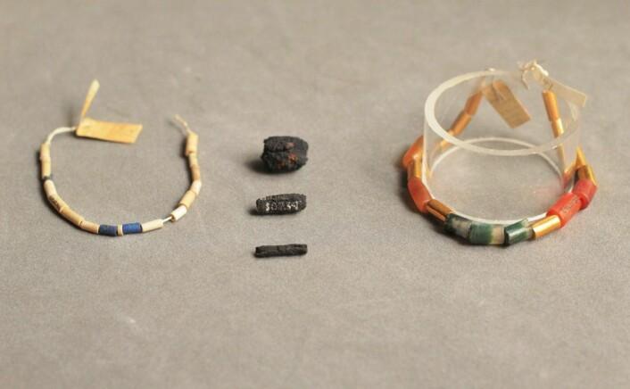 Meteorittjern-bitene ligger i midten av bildet. Bildet viser også sylinderne med blå lasurstein (til venstre), og rødlig karneol, agate og gull (til høyre), som meteorittjern-sylinderne opprinnelig var tredd sammen med. (Foto: UCL Petrie Museum/Rob Eagle)