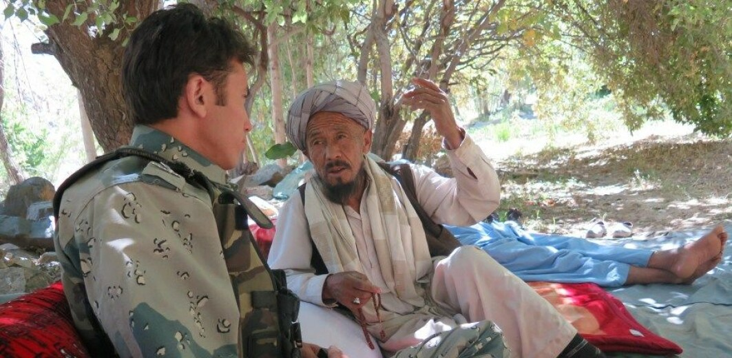 A police officer chatting with an elder who was a member of a group gathered for conflict resolution in Daikundi Province, Afghanistan as part of the Ashterlay peace process.