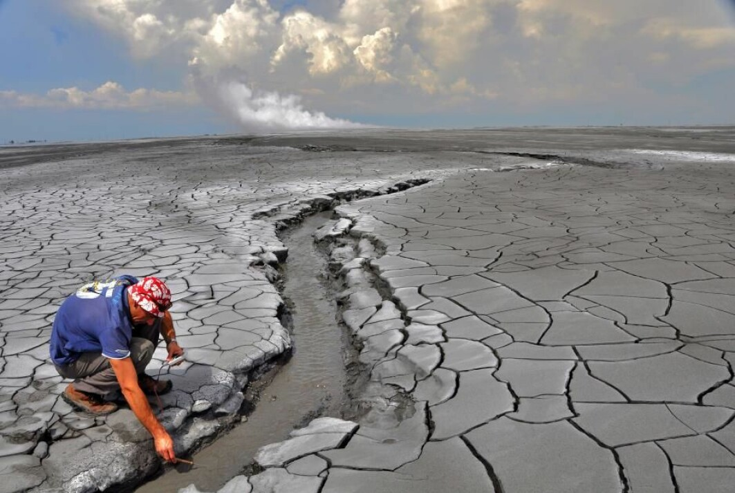 The Lusi eruption: A non accessible 650 m in diameter hot mud pond surrounds the central vents zone (rising plume is seen in the horizon). The erupted mud reaches temperatures of 100 °C and extensive oil slicks can be observed.