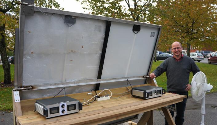 Jo lavere temperatur, desto mer effektive blir solcellene. Her viser førsteamanuensis Espen Olsen hvordan høyre del av solcellen blir avkjølt med vifte, mens venstre del isoleres med plast. (Foto: Arnfinn Christensen)