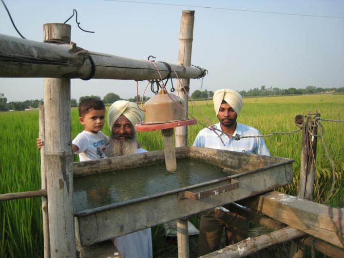 Inderjeet Singh, en av de aktive økobøndene i Punjab, med barnebarnet på skulderen. Sønnen til høyre. De står her bak en insektsfelle som fanger insekter ved hjelp av lys i mørket. Dette er en av teknikkene de økologiske bøndene bruker som alternativ til kjemiske sprøytemidler. (Foto: Anna Marie Nicolaysen)