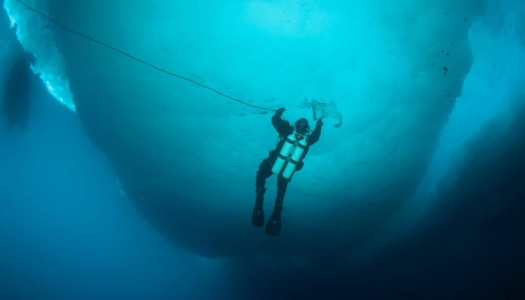 Een duiker controleert het ijs.
