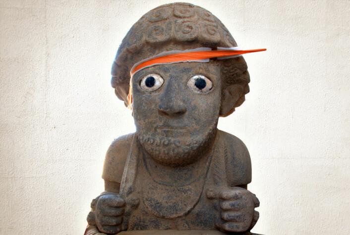 Giganstatue funnet av arkeologer i det sørøstlige Tyrkia. Kun overkroppen er bevart i ett stykke. Den måler 1,5 meter. I hendene holder figuren et spyd og hvetaks. Rundt halsen har den en månesigdformet brystplate. Det oransje båndet er et støttebånd brukt av arkeologene for å sikre statuen. (Foto: Jennifer Jackson/Montasje mot ny bakgrunn: Forskning.no)
