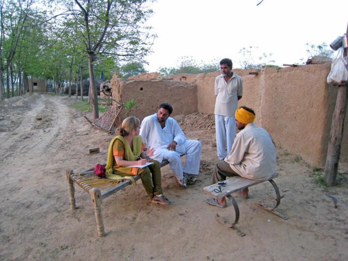 Anna Marie Nicolaysen gjør intervju med en bomullsplukker i Punjab. Bonden og en tolk er også med på bildet. (Foto: Privat)