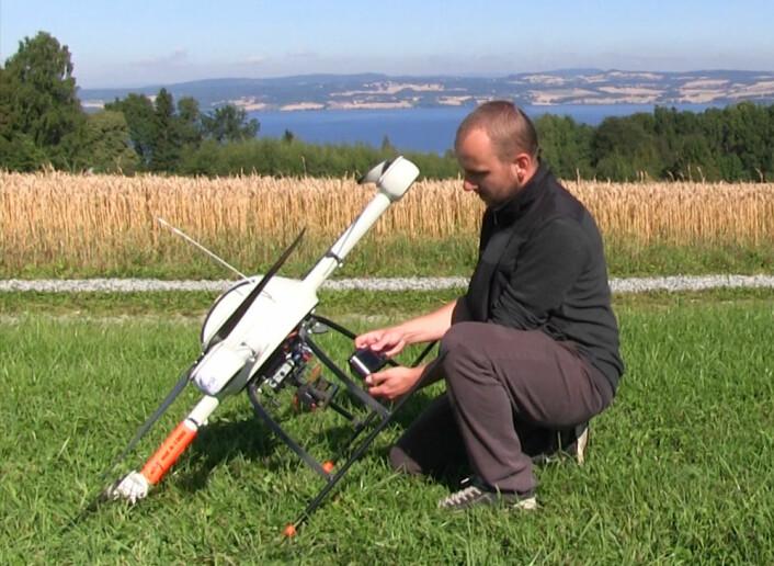 Forsker Krzystof Kusnierek fra Bioforsk Øst gjør robothelikopteret klart for ny fotoferd ved forsøksåkeren på Apelsvoll, Østre Toten. (Foto: Arnfinn Christensen, forskning.no)