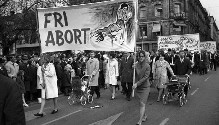 Kvinners liv og helse har lenge vært et viktig tema for de som ønsket å gjøre abort mulig. Her passerer demonstranter med en plakat som skal illustrere hva som kan skje hvis kvinner ikke får mulighet til å ta abort på sykehus. Første mai-toget Stortinget på vei ned Karl Johans gate i 1968.